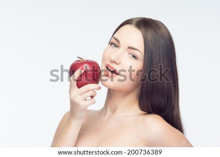 Tremendously beautiful girl keeping very big and tasty apple and going to bite it. Isolated on white background  - stock photo
