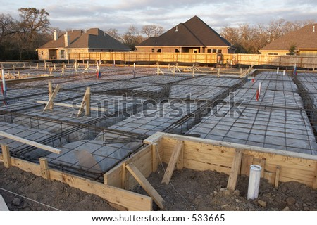 Trenches and rebar prep work for a house foundation. - stock photo