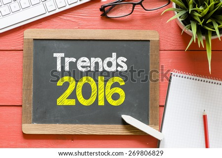 Trends 2016 handwritten on blackboard. Trends 2016 Handwritten with chalk on blackboard, keyboard,notebook,glasses and green plant on wooden background - stock photo