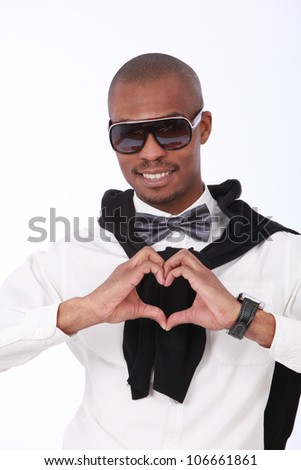 Trendy African American fashionable eccentric man smiling with sunglasses, bow tie,white shirt  and black jersey, with his hands in the shape of a heart close to chest isolated on a white background - stock photo