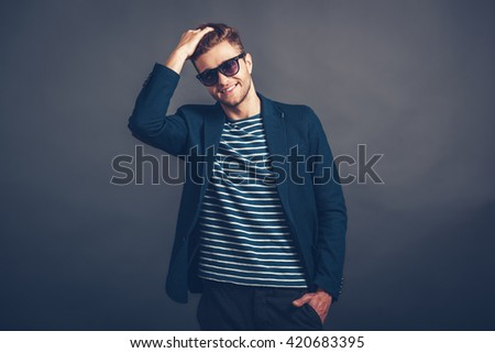 Trendy and charming. Cheerful young handsome man in sunglasses keeping hand in hair and looking at camera with smile while standing against grey background - stock photo