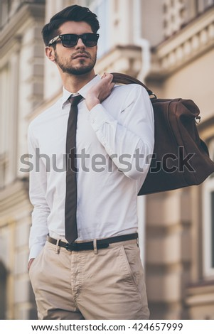 Trendy and handsome. Low angle view of handsome young man in sunglasses holding leather bag and looking away while walking outdoors - stock photo