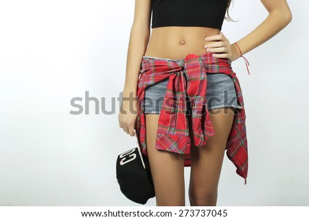 Trendy and stylish beautiful young model posing with urban clothes, over white background.
