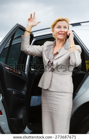 Trendy attractive senior aged business woman 55-65 years with a lovely charming smile, wearing stylish suit, waving his hand and talking on the mobile phone, Positive human emotion, facial expression - stock photo