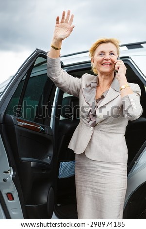 Trendy attractive senior old business woman 55-65 years with a lovely charming smile, wearing stylish suit, waving his hand and talking on the mobile phone, Positive human emotion, facial expression - stock photo