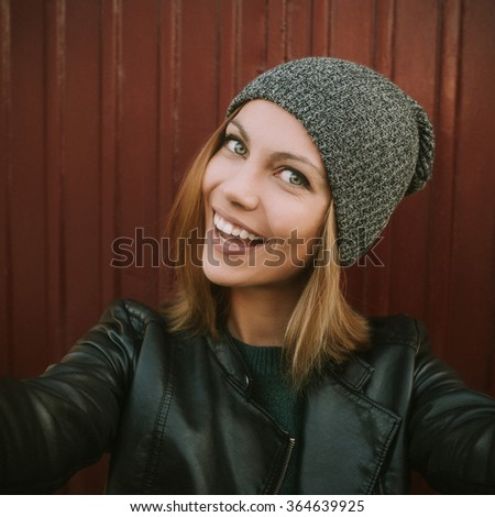 Trendy beautiful cool hipster blond girl wearing a gray hat, black leather jacket taking selfie. Smiling girl. Urban style. Edited with filter. - stock photo