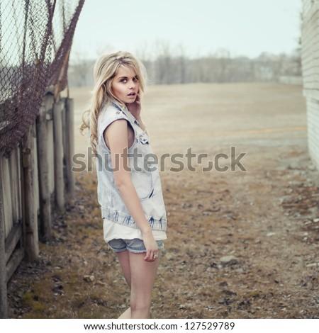 trendy beautiful girl posing in an urban slum - stock photo