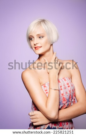 Trendy blond woman in front of purple backgroun  - stock photo