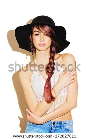 Trendy boho fashion young Caucasian woman wearing white crochet fringe bikini top, black fedora, denim jeans and black tassel bag on isolated white background. Fashion concept, vertical, retouched. - stock photo