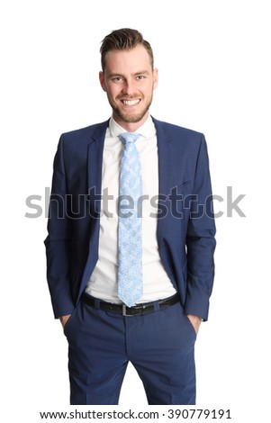 Trendy businessman standing against a white background wearing a blue suit, white shirt and a light blue tie. Staring at camera. - stock photo