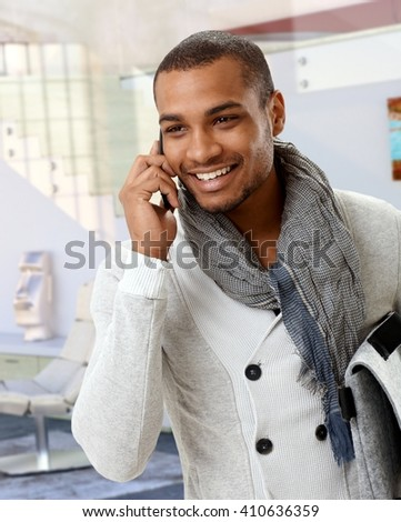 Trendy casual afro american man talking on mobile phone at home. Smiling, standing. - stock photo