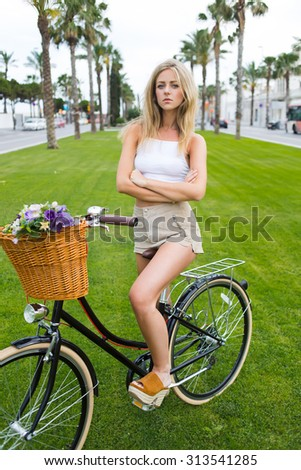 Trendy caucasian woman in stylish clothing sitting on her vintage bike in pose with hands crossed while standing on the green grass in the park, wonderful female posing with classic bicycle outdoors - stock photo