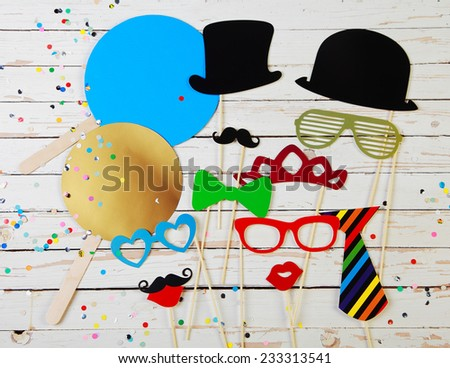 Trendy colorful party background of fun photo booth accessories for comic disguise and multicolored confetti on rustic white wooden boards - stock photo