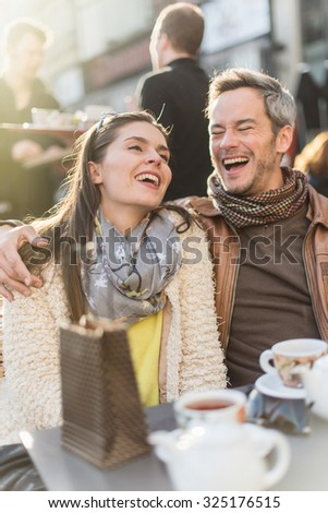 Trendy couple having fun and sitting at a terrace in the city center. The woman is wearing a woolen coat and a scarf The grey hair man has a beard and a leather coat A shopping bag is on the bar table - stock photo