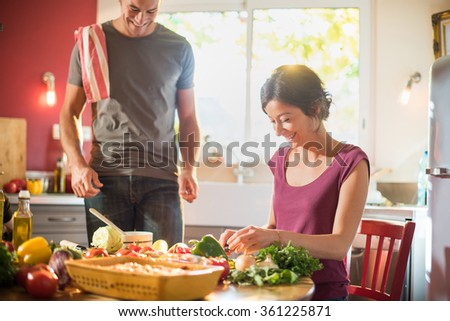 Trendy couple in casual clothes cooking vegetables from the market in a red kitchen. The grey hair man is cooking the sauce in a white pan while the woman is taking care of the fresh vegetables. - stock photo