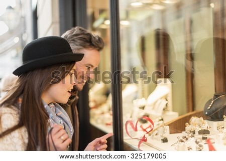 Trendy couple is looking at engagement rings. A grey hair man with beard and a woman with a black hat are standing in front of a jewelry shop. The woman is showing a ring on the shop window. - stock photo