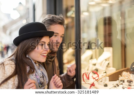 Trendy couple is looking at engagement rings. A grey hair man with beard and a woman with a black hat are standing in front of a jewelry shop. They are looking at the shop window.