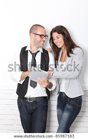Trendy couple leaning on wall with electronic tablet - stock photo