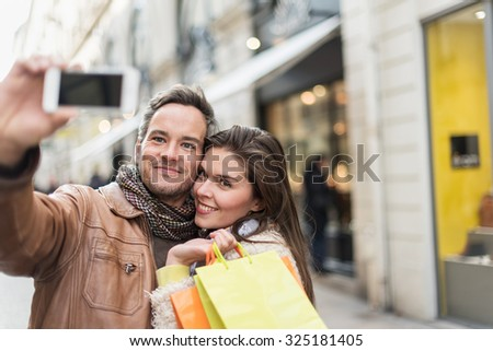Trendy couple taking selfies with their smartphone in the city center. The grey hair man is wearing a scarf and a leather coat and the woman is holding two shopping bags. Focus on the couple