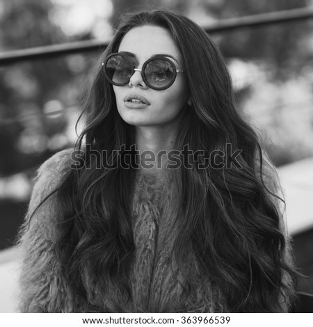 Trendy drssed fashionable girl wearing fur coat. Young pretty beautiful woman with long curly hair looking at you. - stock photo