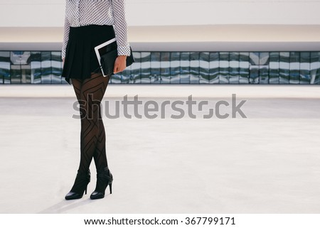 Trendy fashion business woman holding digital tablet outside corporate building. Unrecognizable businesswoman standing with digital device and handbag wearing stylish professional clothing. - stock photo