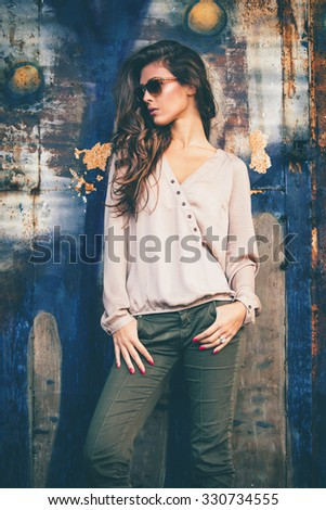trendy fashion girl in silky beige shirt, green pants and sunglasses stand in front old rusty grunge metal door, outdoors - stock photo
