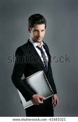 Trendy fashion young businessman black suit casual tie on gray background - stock photo