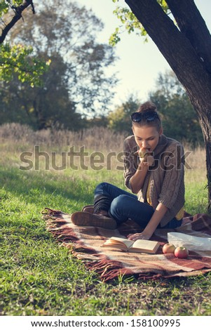 trendy girl enthusiastically reading a book and eating an apple during the picnic. sitting near the tree in the park