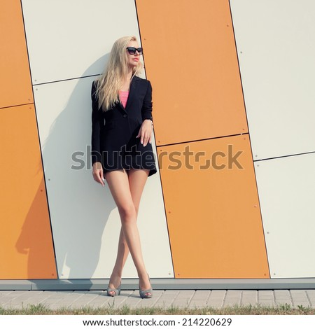 trendy girl in a black jacket and sunglasses posing on the background color of orange wall - stock photo