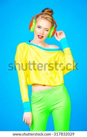 Trendy girl in bright colorful clothes listening to music in headphones. Party style. Fashion studio shot. - stock photo