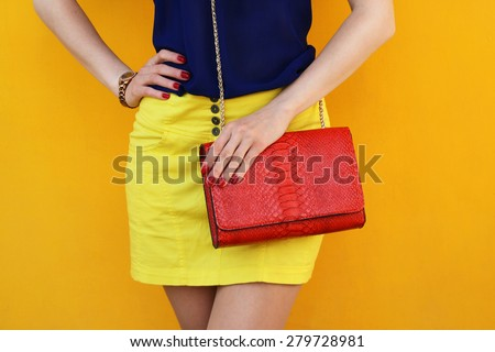 Trendy girl in yellow skirt with red leather bag . Stylish outfit and fashion concept - stock photo