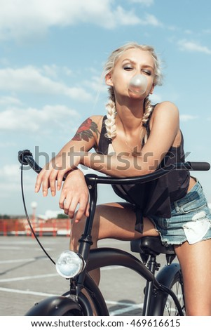 Trendy Girl inflating a bubble gum sitting on bicycle on Urban Background. Modern Youth Lifestyle Concept
