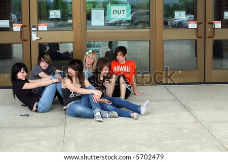 trendy group of teens outside school entrance - stock photo