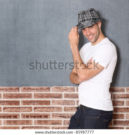 Trendy guy on urban background - stock photo