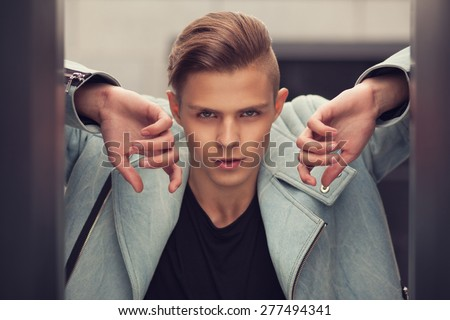 Trendy handsome guy with trendy hairstyle outdoors - stock photo