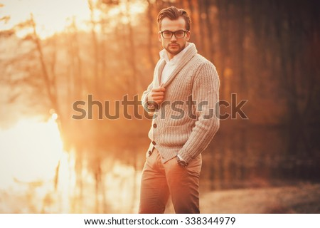 Trendy handsome man posing in autumn park alone - stock photo