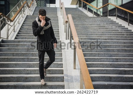 Trendy handsome young man in winter fashion standing on a long staircase leading to an urban commercial building looking down with a serious expression