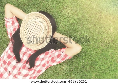 Trendy hipster asian woman relaxing on the green grass with hat on her face. Relaxing concept. Vintage tone Retro filter effect,soft focus.