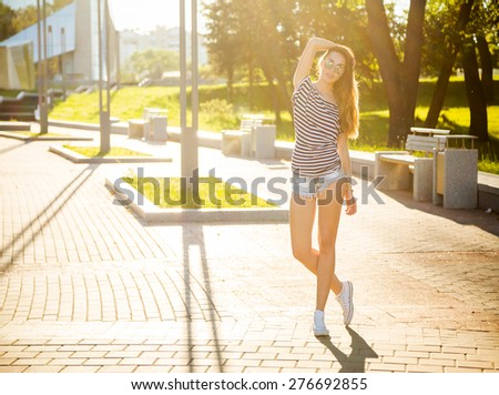 Trendy Hipster Girl Posing Outdoors. Summer Sunlight Background. Toned and Filtered Photo with Backlit. Free Youth Lifestyle Concept. - stock photo