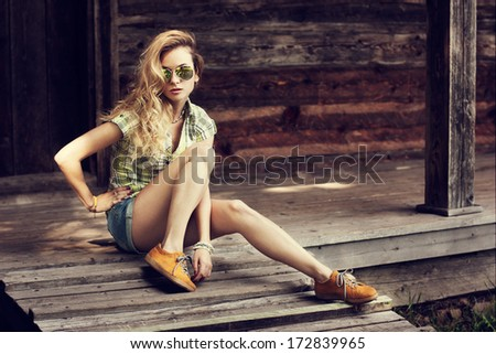 Trendy Hipster Girl Sitting on the Wooden Porch. Toned Photo. Modern Youth Lifestyle Concept. - stock photo