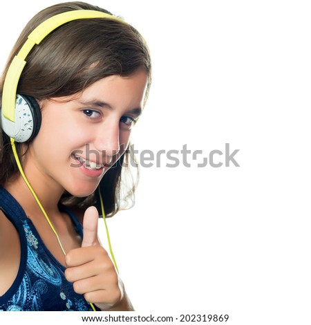 Trendy hispanic teenager listening to music on her headphones while doing a thumbs up sign isolated on white - stock photo
