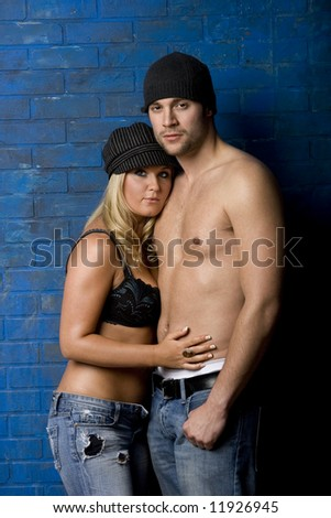 Trendy intimate couple standing against blue brick wall - stock photo