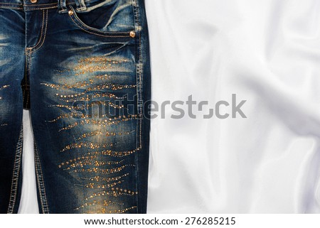 Trendy jeans with rhinestones lies on white silk, with space for your text - stock photo