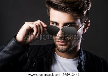 Trendy look. Handsome young man adjusting his sunglasses and looking at camera while standing against black background - stock photo
