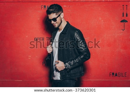 Trendy look. Handsome young man in sunglasses adjusting his jacket and looking away with smile while standing against red background - stock photo