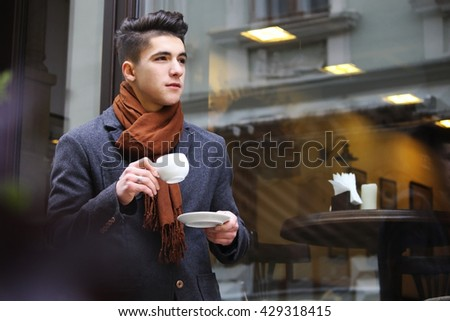 Trendy man with a cup of coffee near a storefront. - stock photo