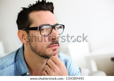 Trendy man with hand on chin looking at camera