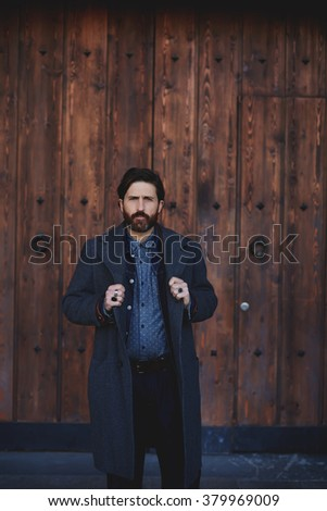 Trendy mature man dressed in cashmere coat posing against wooden background for cover of fashion magazine, stylish adult male with serious look standing outdoors during recreation time in autumn day  - stock photo