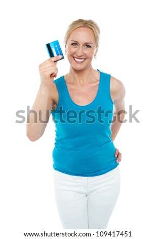 Trendy middle aged woman showing credit card to camera with hand on her waist - stock photo