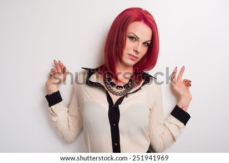 Trendy model with vivid red hair posed against a white wall - stock photo